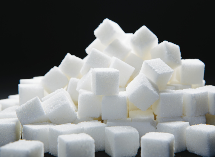 Pile of sugar cubes against a black backdrop.